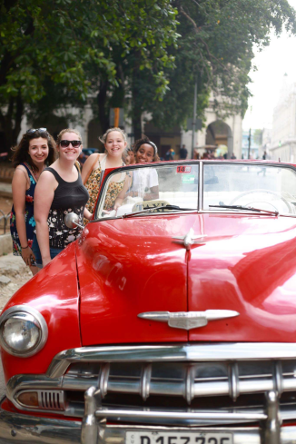 A classic red Chrysler convertible that serves as a taxi in Havana.